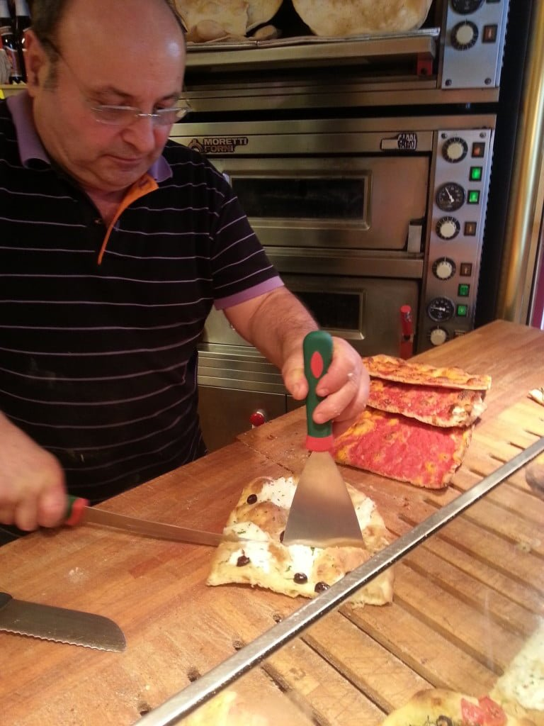 Our friendly local pizzaiolo cutting a slice